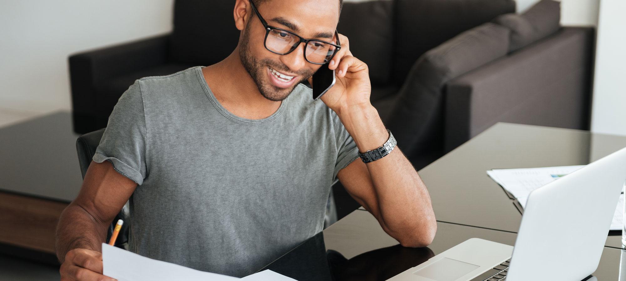 Smilende mann som snakker på telefonen