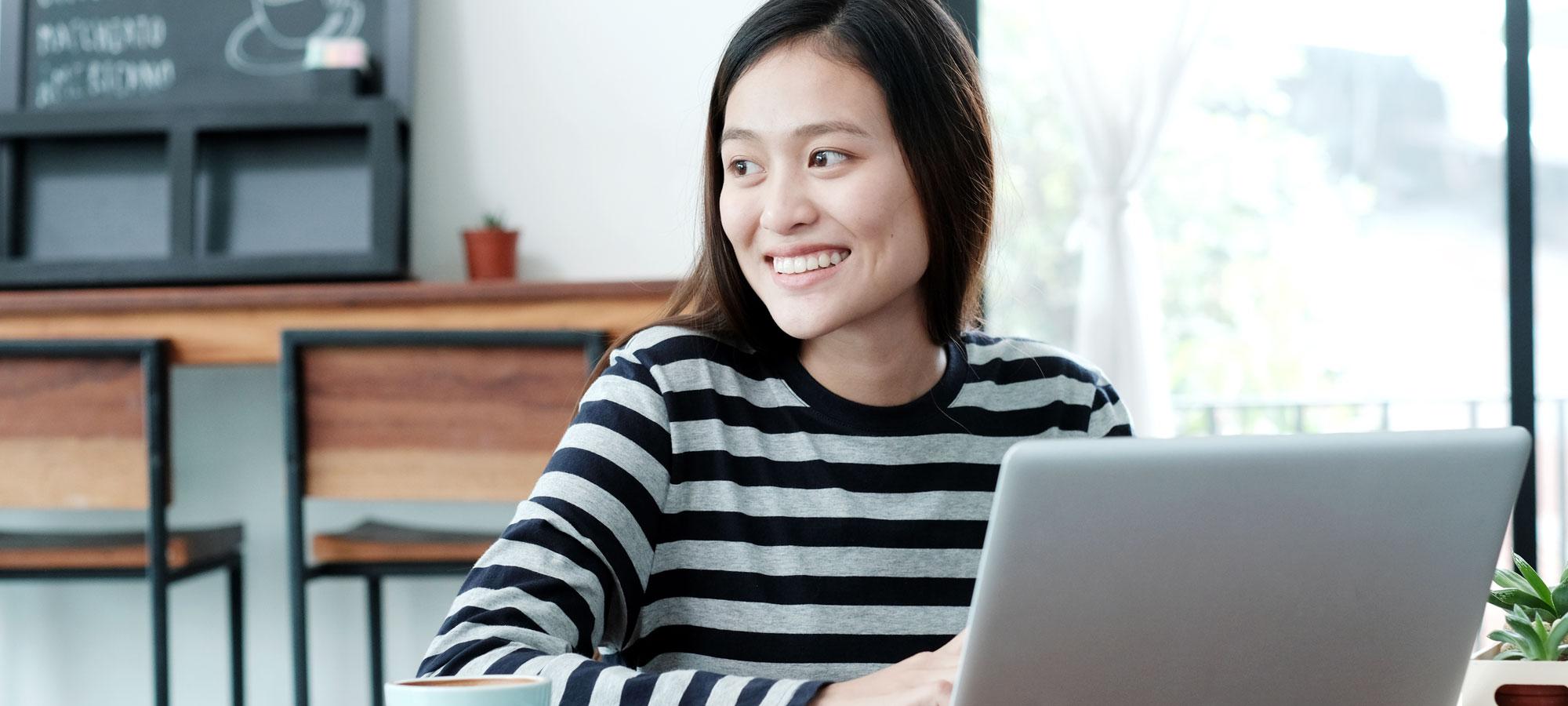Kvinne som jobber på laptop i en kafé