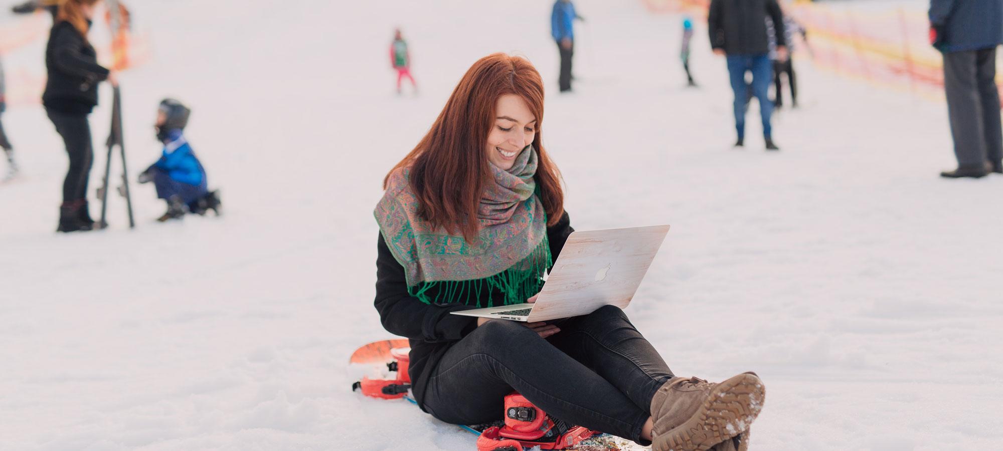 Kvinne som arbeider på PC ute på et snowboard